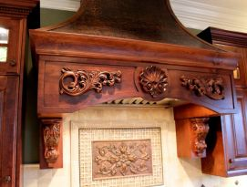 Beautiful hood above stove with wood carvings and hammered copper