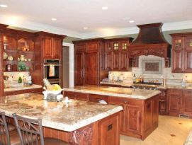Alder cabinetry with detailed carvings and two islands