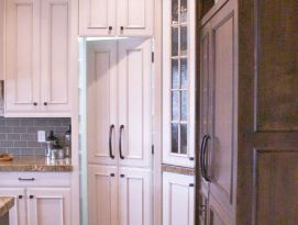 White cabinetry with hidden pantry door