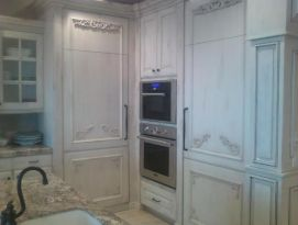 White kitchen cabinetry with beautiful carvings