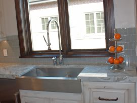 Stainless steel farm sink with white cabinetry in front of a large wood framed window.