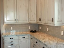 White cabinetry with quartz counter top, tiled back splash and hardwood flooring.