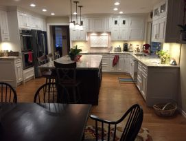 White kitchen cabinets with black island and hardwood floors
