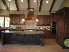 Wood kitchen cabinetry with black island and beautiful hammered copper hood