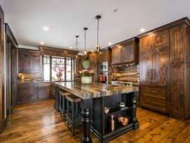 Wood kitchen cabinetry with black island