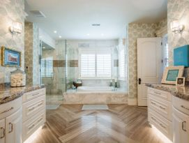 Master bath with chevron wood floor, white cabinets and garden tub