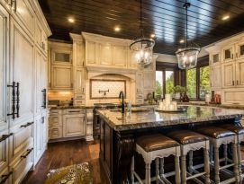 White kitchen cabinets with dark island, floor and wood plank ceiling