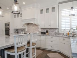 White kitchen cabinetry with gray island, back splash and counter tops