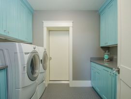 Bright aqua color on cabinetry with gray counter top in this laundry room