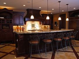 Dark alder wood kitchen with beautiful carvings on corbels and hood.