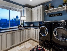 Laundry room featuring white cabinetry with bead board doors and drawers with dark glaze