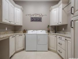 Laundry room with white, glazed and distressed cabinetry