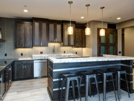 Wet bar in quarter sawn oak with gray stain. Metal mesh in top cabinets with stainless steel paneled into the bar seating area and floating shelves.