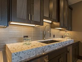 Wet bar with raised granite counter top and metal mesh in the top cabinets