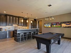 Kitchenette/bar with pool table and wall of three tvs.
