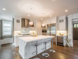 White kitchen cabinetry and counter tops with hardwood floor