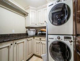 White cabinetry with dark glaze and dark granite counter tops in this laundry room