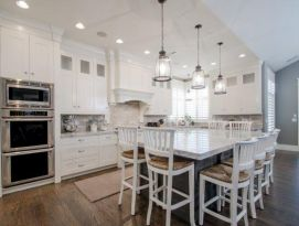White kitchen cabinetry with gray island, back splash, counter tops and stainless appliances