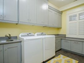 Laundry room with gray cabinetry dark gray counter tops and happy yellow walls