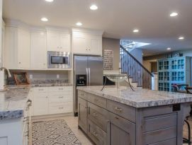 White kitchen cabinetry with gray island and gray granite counter tops