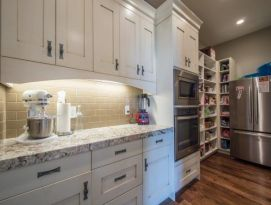 walk in pantry with white shaker style cabinetry