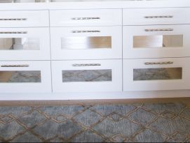 Butler pantry with white cabinetry and counter tops and mirrored drawers