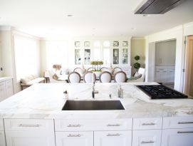 White kitchen island with cook top and sink in front of white hutch