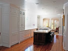 White kitchen cabinetry with dark wood island.